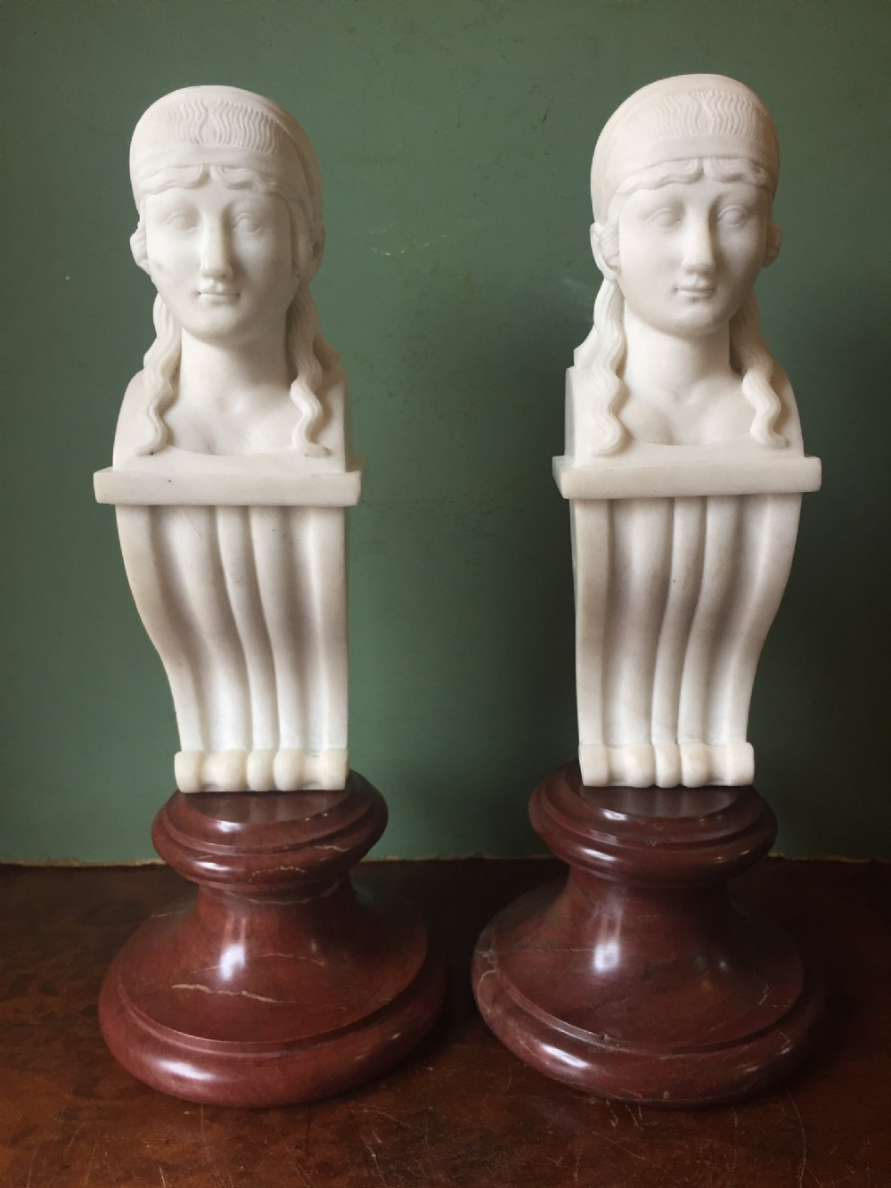 pair of early c19th regency period carved statuary marble female term figures in the manner of thomas hope mounted upon rouge marble socles