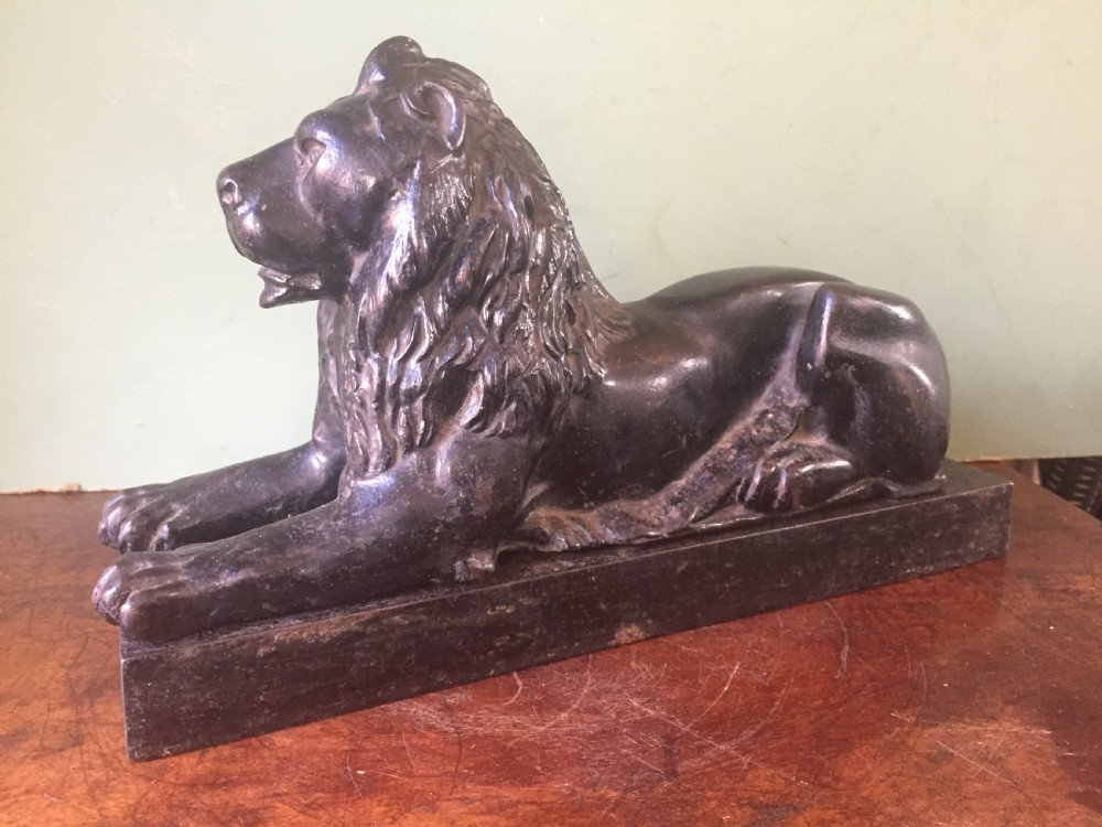 late c19th castiron model of a recumbent lion on a rectangular plinth base